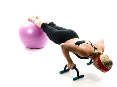 push ups:  illustration of push ups on fitness core training ball with push up bars by attractive middle age fitness trainer teacher woman exercising and stretching