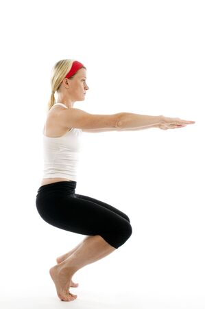 middle age women: yoga awkward pose illustrated by attractive middle age fitness trainer teacher woman exercising and stretching Stock Photo