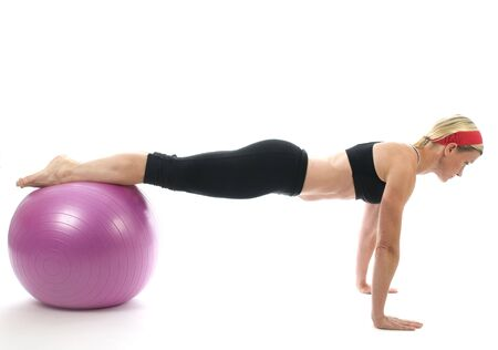 push up: illustration of push ups on fitness core training ball with push up bars by attractive middle age fitness trainer teacher woman exercising and stretching