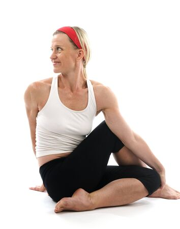 yoga spine twisting vikram pose illustrated by attractive middle age fitness trainer teacher woman exercising and stretching