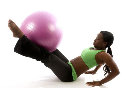 young and pretty hispanic latina black woman wearing exercise tights and working out  leg raises ab exercises with fitness core ball photo