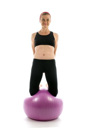 sit ups: attractive middle age trainer woman doing balance exercise on fitness core training ball Stock Photo