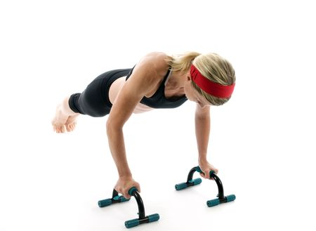 aantrekkelijk middelbare leeftijd vrouwelijke fitnesstrainer oefenen met fitness-push up bars