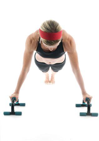 aantrekkelijk middelbare leeftijd vrouwelijke fitnesstrainer uitoefening push ups fitness push up bars vooraanzicht Stockfoto