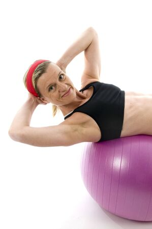 sit:  attractive middle age trainer woman doing sit ups on fitness core training ball