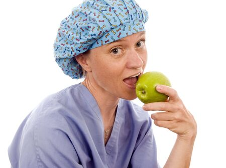 nurse or doctor medical woman eating a healthful fresh fruit granny smith green apple photo
