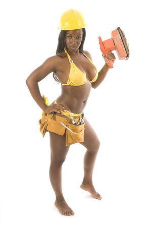 young and pretty hispanic latina black woman wearing bikini swim suit and working construction with tools and hard hat helmet Stock Photo