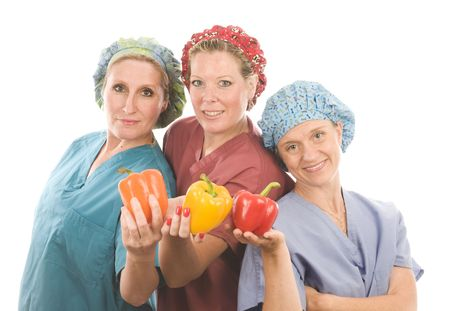 team of female nurses or doctors promoting healthy diet with fruits and vegetables photo