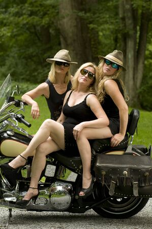 three sexy attractive middle age blond women on large motorcycle dressed like secret agent spies  in black clothes photo