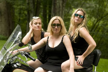 three sexy attractive middle age blond women on large motorcycle in black clothes photo