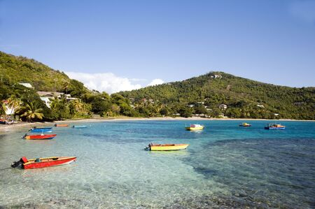 grenadines: colorful native made wood fishing boats on friendship bay with mountains and tropical landscape bequia st. vincent and the grenadines in the caribbean sea Stock Photo
