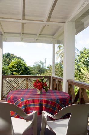 dining table on outdoor patio deck with view of tropical jungle and caribbean sea at budget guest house motel in bequia island st. vincent and the grenadines Stock Photo - 6086968