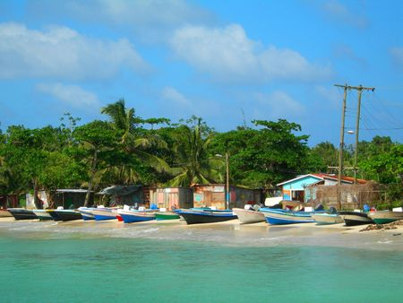 native panga fishing boats on beach with native zinc houses brig bay corn island nicaragua central america photo