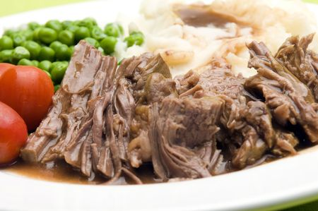 sliced pot roast beef dinner with peas mashed potatoes and gravy
