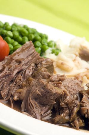 mashed potatoes: sliced pot roast beef dinner with peas mashed potatoes and gravy