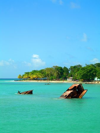 corn island: rusting wreck of sunken ship on caribbean sea shores of corn island nicaragua with natives playing soccer on the beach