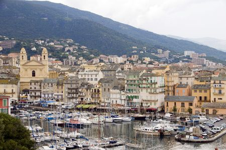 the old port of Bastia Corsica France with St. John the Baptist historic church and shops restaurants cafes and yachts boats in the harbor with condos and medieval buildings