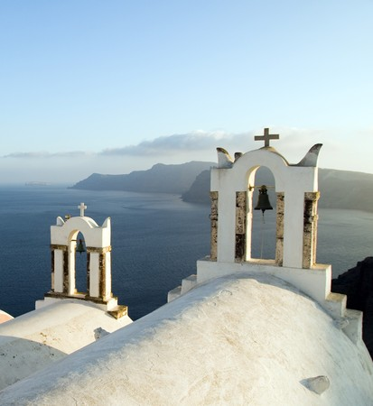 ia: white-washed stucco twin bell tower church over the mediterranean sea volcanic caldera cliffs Oia Ia Santorini Thira Cyclades island Greece