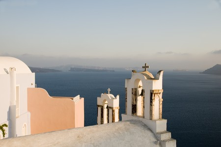 white-washed stucco twin bell tower church and traditional house over the mediterranean sea volcanic caldera cliffs Oia Ia Santorini Thira Cyclades island Greece Stock Photo - 7145481