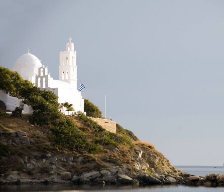 classic white church with Greek flag at mouth of harbor Ios Cyclades island Greece Stock Photo - 7179291