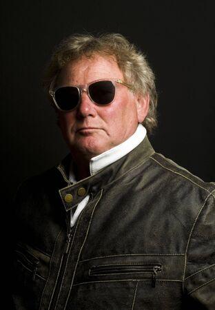 handsome middle age senior man sunglasses wearing black leather motorcycle jacket photo