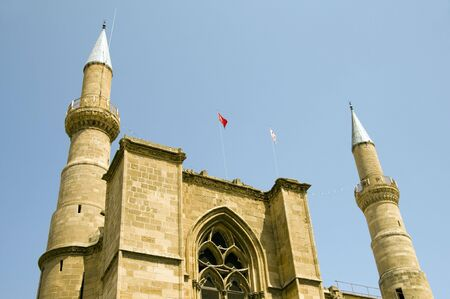 detail of st. sophia cathedral selimiye mosque with minarets and both turkish and cyprus flag in divided capital lefkosia nicosia cyprus in the mediterranean Фото со стока