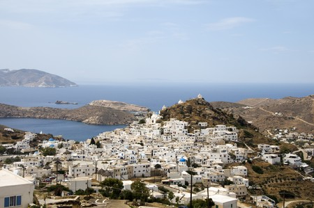 white washed: panoramic landscape of typical Greek island architecture white washed Cyclades buildings churches with view of Mediterranean sea harbor Ios island Greece  Stock Photo