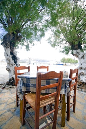 typical taverna restaurant table with woven Greek chairs seaside in Antiparos Island Cyclads Greek islands Фото со стока