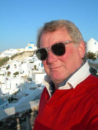middle age male tourist in the Greek Islands Santorini with Cyclades architecture and church photo