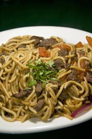 Peruvian style beef spaghetti pasta with basil leaves called tallarin saltado de carne