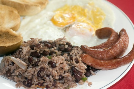 pinto beans: typical breakfast in Nicaragua gallo pinto rice beans sausage eggs and toast as photographed in Corn Island Stock Photo