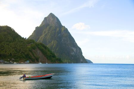 lucia: Caribbean Sea native fishing boat  with view twin piton peaks and volcano mountains  Soufriere St. Lucia island West Indies Stock Photo