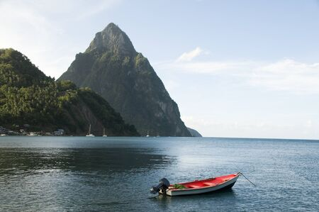 Caribbean Sea native fishing boat  with view twin piton peaks and volcano mountains  Soufriere St. Lucia island West Indies Archivio Fotografico