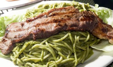 steak pesto tallarin lomo saltado traditional Peruvian pasta dish with green spaghetti