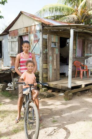 poor people: mother daughter on bicycle in front of clapboard house in poverty of Big Corn Island Nicaragua Central America Stock Photo