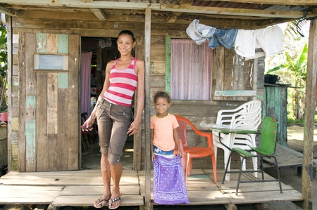 幸せな母娘ポーチ貧困大きなトウモロコシ島ニカラグア中央アメリカの下見板張りの家の前に笑みを浮かべてください。 写真素材