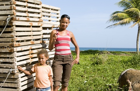 lobster pot: Hispanic mother daughter by lobster pot traps Caribbean Sea Big Corn Island Nicaragua Central America