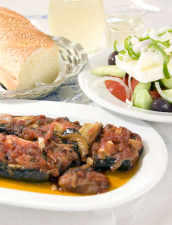 Greek taverna food specialty eggplant stuffed with feta cheese tomatoes sauce with Greek salad crusty bread and house wine as photographed in Syros Greece Stock Photo - 9913977