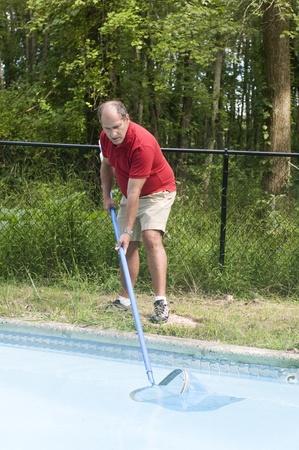 skimming: nataci�n due�o de una casa de mantenimiento de piscinas hombre de la limpieza piscina rozando los escombros del agua Foto de archivo