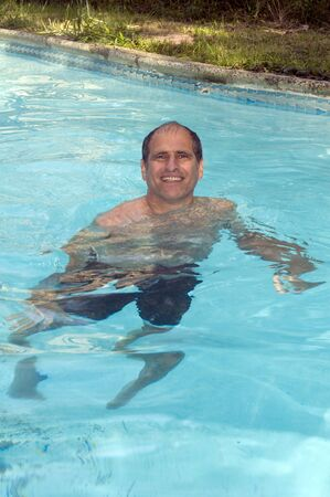 inground: handsome smiling middle age man swimming in suburban house private swimming pool Stock Photo
