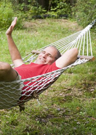 smiling middle age man relaxing in hammock in suburban backyard Stock Photo - 10539163