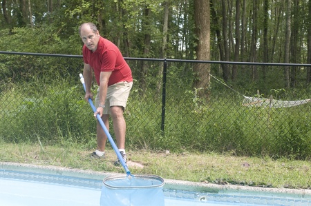 inground: homeowner swimming pool maintenance man cleaning swimming pool skimming debris from water horizontal composition Stock Photo