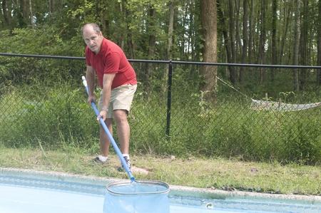 skimming: nataci�n due�o de una casa de mantenimiento de piscinas hombre de la limpieza piscina rozando los escombros de la composici�n del agua horizontal Foto de archivo