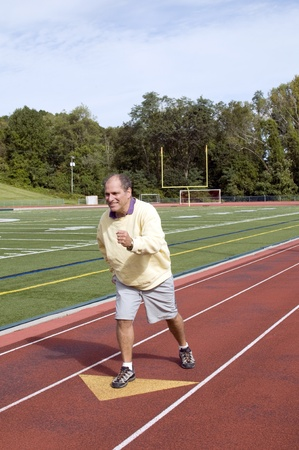 handsome middle age senior man stretching exercising running jogging on sports football field and running track photo