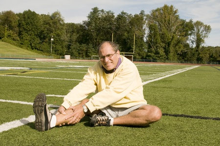 handsome middle age senior man stretching exercising on sports field photo