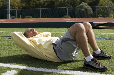 sit: handsome middle age senior man stretching exercising sit ups ab abdominal exercise on sports field