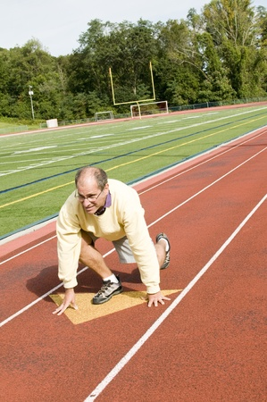 handsome middle age senior man stretching exercising on sports football field and running track photo