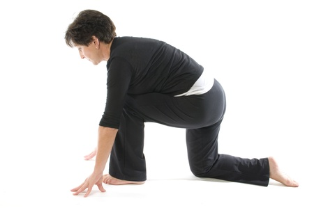 hamstring: middle age senior woman demonstrating yoga position Anjaneyasana Kneeling quadriceps Lunge & Hamstring Stretch Stock Photo