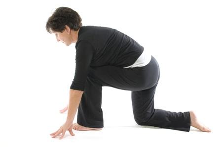 kneeling woman: middle age senior woman demonstrating yoga position Anjaneyasana Kneeling quadriceps Lunge & Hamstring Stretch Stock Photo