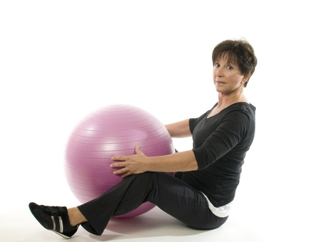 health and fitness: middle age senior woman fitness exercise with core training ball sit ups